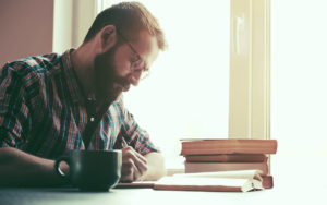 Header - Man Writing on Desk